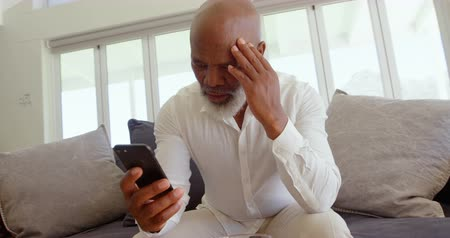 domácké : Front view of mature black man sitting on the couch and using mobile phone in a comfortable home. He is upset and stressed out 4k