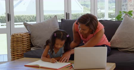 mentorat : Front view of mature black mother helping her daughter with homework in a comfortable home. She is drawing sketch on book 4k Vidéos Libres De Droits