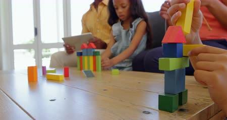 wełna : Children playing with building blocks on table in a comfortable home. Mother knitting and father working on digital tablet 4k Wideo