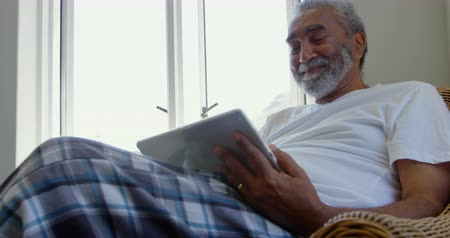 positive ageing : Front view of senior black man sitting on the couch and using digital tablet in comfortable home. He is smiling and optimistic 4k