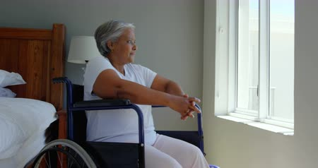 physically : Side view of handicap senior black woman sitting on wheelchair near window in bedroom at home. She is looking outside through window 4k