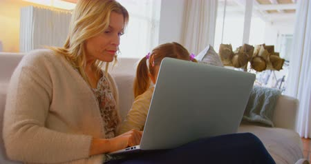 quarter : Side view of young Caucasian mother teaching daughter using laptop in a comfortable home. They are sitting on the couch 4k