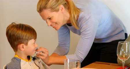 homely : Front view of young Caucasian mother is wiping the sons mouth with a napkin cloth at dining table. She is smiling and talking 4k