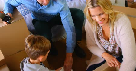 belongings : High angle view of Caucasian family packing their belongings in a comfortable home. Son putting belongings in cardboard box 4K 4k Stock Footage