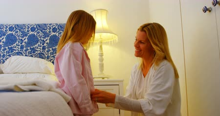 girl in robe : Side view of young Caucasian mother helping her daughter to wear a cloth in bedroom at home. She is smiling and looking at her 4k Stock Footage