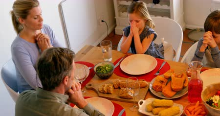 clasped : High angle view of Caucasian family praying together at dining table in a comfortable home. They are eyes closed and holding hands 4k