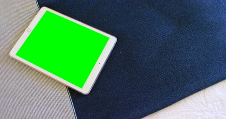 tenso : Close-up of digital tablet on table at home. Green screen on digital tablet 4k
