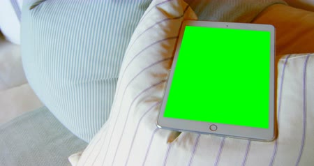 tenso : Close-up of digital tablet on cushion at home. Green screen on digital tablet 4k Vídeos