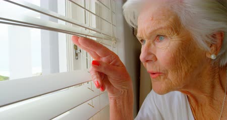 70年代 : Close-up of Caucasian senior woman looking through window blinds at home. She is curious and eager 4k