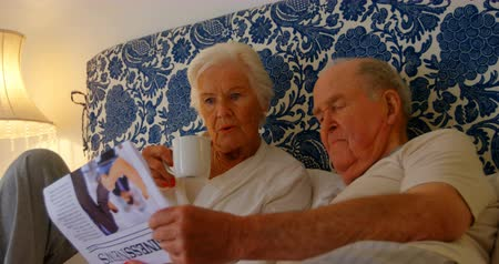 holding newspaper : Front view of Caucasian senior couple reading news paper on bed in bedroom at comfortable home. They are relaxing and drinking coffee 4k