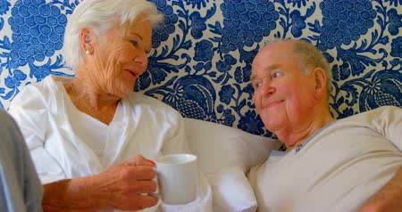 active ageing : Front view of Caucasian senior couple interacting with each other on bed at comfortable home. They are relaxing on bed 4k