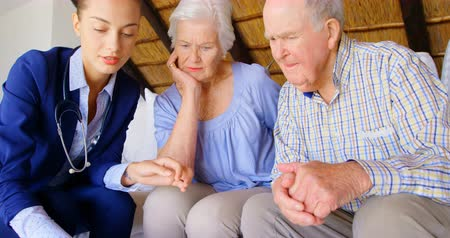 arbustos : Front view of Caucasian female doctor discussing medication with senior couple at comfortable home. Caucasian female doctor showing pills to senior couple 4k