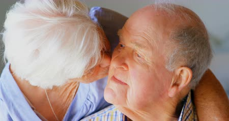bochecha : Close-up of Caucasian senior woman kissing senior man at comfortable home. They are embracing at home 4k