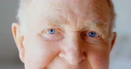 positive ageing : Close-up of Caucasian senior man looking at camera in a comfortable home. He is smiling 4k