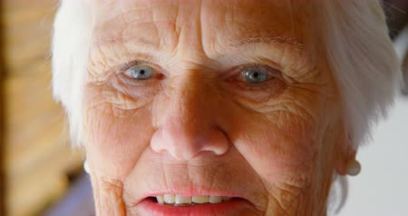 positive ageing : Close-up of Caucasian senior woman looking at camera in a comfortable home. She is smiling 4k Stock Footage