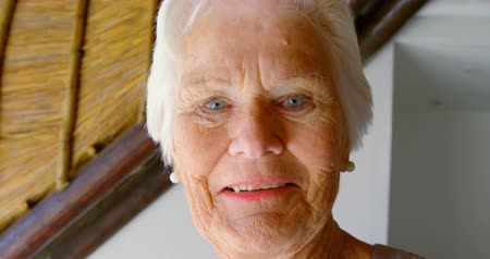 positive ageing : Close-up of senior woman looking at camera in a comfortable home. She is smiling 4k Stock Footage