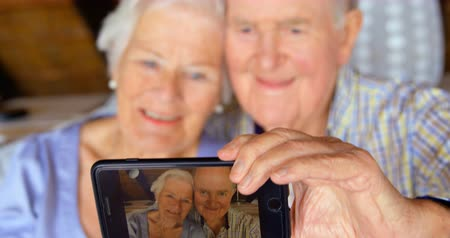 důchodce : Front view of old Caucasian senior couple taking selfie with mobile phone at comfortable home. They are smiling and relaxing at home 4k Dostupné videozáznamy