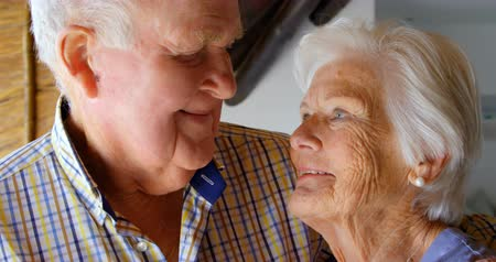 positive ageing : Close-up of old Caucasian senior couple looking at each other in a comfortable home. They are embracing each other 4k