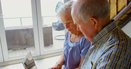 70年代 : Side view of Caucasian senior couple using laptop at comfortable home. They are interacting with each other 4k