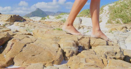ona : Low section of woman walking on the beach. She is walking barefoot on the rocks 4k