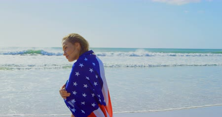 envolto : Side view of young Caucasian woman wrapped in American flag on the beach. She is smiling and lookinmg away 4k Vídeos