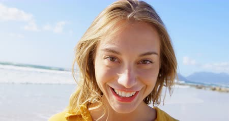 ona : Front view of young Caucasian woman standing on the beach. She is smiling and looking at camera 4k