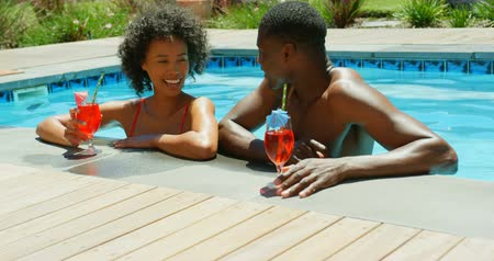 saman : Front view of young black couple toasting glasses of cocktail in the swimming pool at resort. They are relaxing in swimming pool 4k