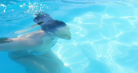 basen : Side view of young mixed-race woman taking a dip in swimming pool on a sunny day. She is swimming in pool 4k Wideo