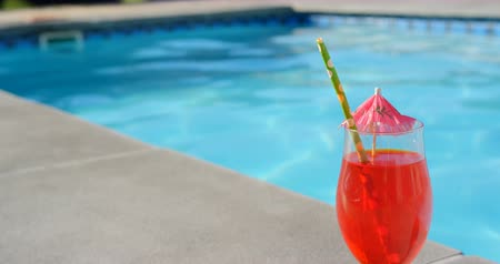 hoogspringen : Close-up of cocktail glass with umbrella and straw near swimming pool. Woman jumping in swimming pool in the background 4k Stockvideo