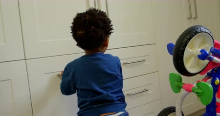 infância : Side view of cute little black son playing in a comfortable home. Mother hand spinning tricycle wheel 4k