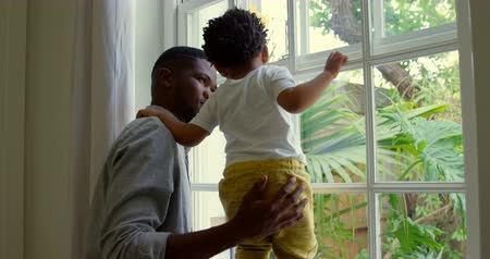 sill : Side view of young black father playing with his son on window sill in a comfortable home. He is holding and looking his son 4k Stock Footage