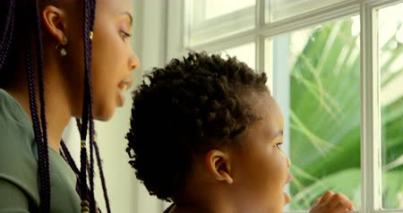 sill : Close-up of young black mother playing with his son on window sill in a comfortable home. She is kissing her son 4k