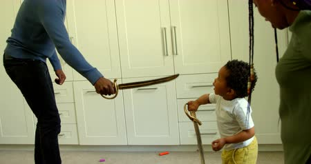 kard : Side view of young black father and son playing with toy sword in a comfortable home. Mother standing and looking them 4k Stock mozgókép