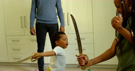 kard : Side view of young black mother and son playing with toy sword in a comfortable home. Father holding son hands 4k
