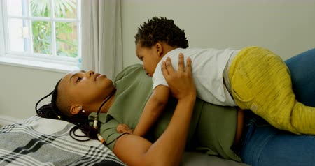 dreadlock : Side view of young black mother playing with her son on bed in a comfortable home. Son lying on mother body 4k Stock Footage