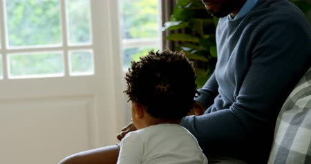 waking : Side view of cute little black son waking from fathers lap while sitting on the couch in a comfortable home. Father holding laptop 4k