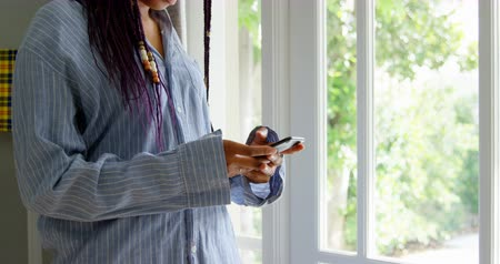 tárcsázás : Side view of young black woman talking mobile phone and standing in a comfortable home. She is dialing and looking outside 4k