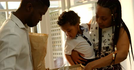 buttoning : Front view of young black mother and son looking in grocery bag in kitchen of comfortable home. Father holding grocery bag 4k