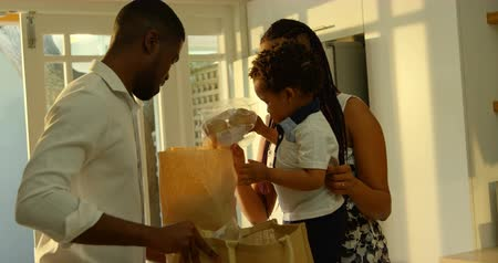 buttoning : Side view of young black mother and son looking in grocery bag in kitchen of comfortable home. Father holding grocery bag 4k