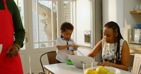 két : Front view of black young mother working on laptop and son playing at dining table in kitchen. Father standing and holding bowl 4k