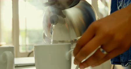 vízforraló : Close-up of black woman pouring hot water in coffee cup at dinning table in kitchen. Steam coming out of coffee cup 4k Stock mozgókép