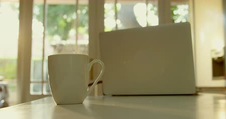 absence : Close-up of mug of coffee and laptop on dining table in kitchen of comfortable home. Steam coming out of coffee mug 4k