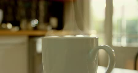 absence : Close-up of mug of coffee on dining table in kitchen of comfortable home. Steam coming out of coffee mug 4k Stock Footage