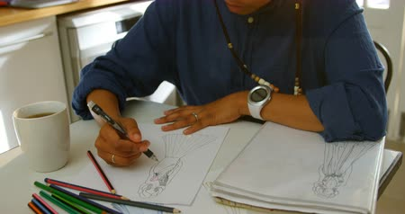 ona : High angle view of young black female fashion designer drawing sketches of dress at dining table. She is using drawing pencil and drinking coffee 4k Dostupné videozáznamy