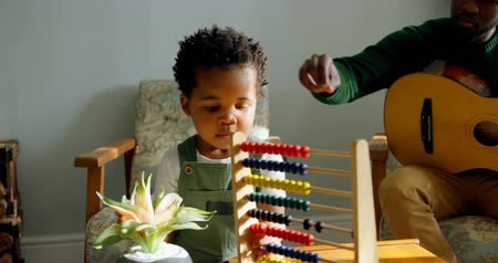 acariciando : Front view of cute little black son playing with abacus in living room of comfortable home. Father with guitar sitting on chair and caressing son hair 4k