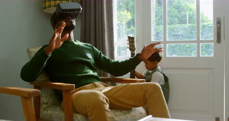 guitarrista : Front view of young black father using virtual reality headset in a comfortable home. Son playing with guitar 4k