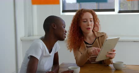 conference table : Front view of young mixed-race business team working on digital tablet in a modern office. They are drinking coffee and discussing 4k Stock Footage