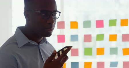 pegajoso : Side view of young black businessman talking on mobile phone in a modern office. Sticky notes on a glass wall 4k