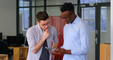 megbeszélés : Front view of young mixed-race business team working on digital tablet in a modern office. They are planing and discussing 4k Stock mozgókép