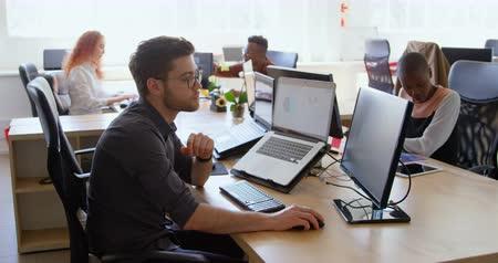 mys : Side view of young cool mixed-race business team working at desk in a modern office. They are using laptop and desktop pc 4k Dostupné videozáznamy